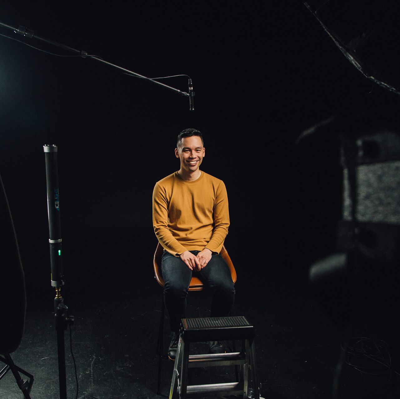 An image of Brandon Yan during the filming of his video. He is sitting on a chair in front of video cameras and studio lighting.