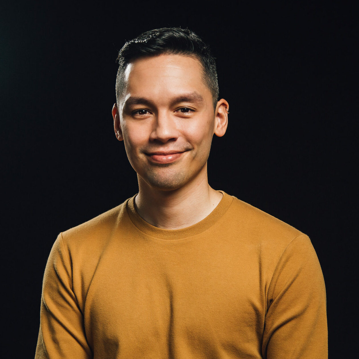 A portrait of Brandon Yan who is of mixed Asian and White ancestry. He is wearing a yellow sweater and has short, dark hair.