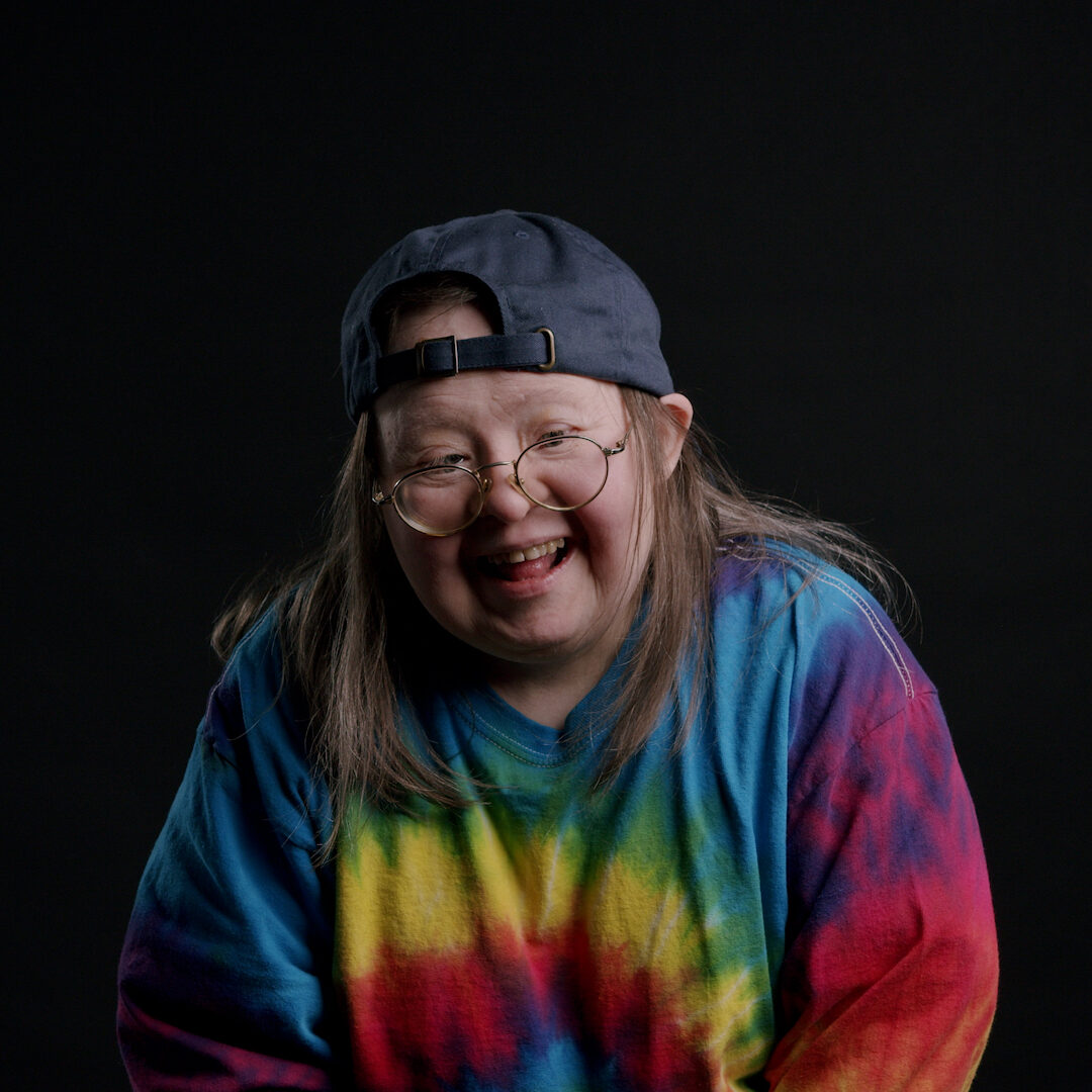A portrait of Teresa Pocock. She is a white woman wearing a blue baseball cap and a tie-dye shirt.