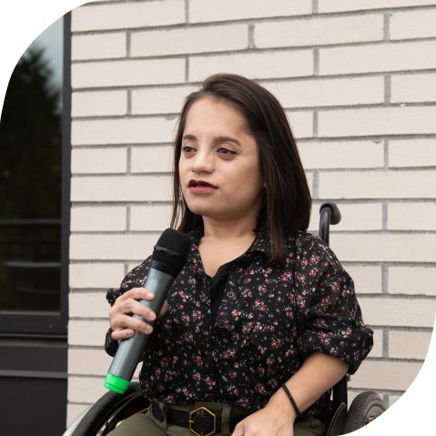 A South Asian person is in her wheelchair sitting in front of a brick wall, holding a microphone while giving a speech.
